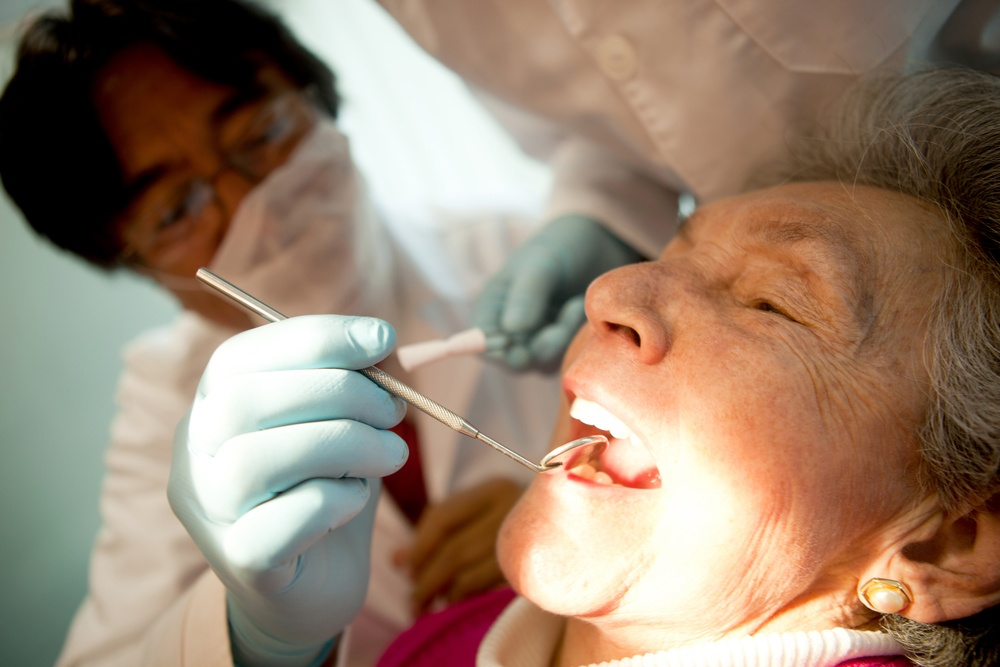 Old woman visiting the dentist taking care of her teeth